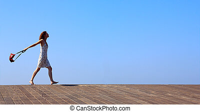 young girl goes barefoot and swinging a bag