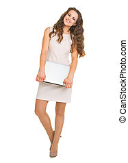 Full length portrait of smiling young woman with laptop