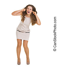 Full length portrait of frustrated young woman closing ears...