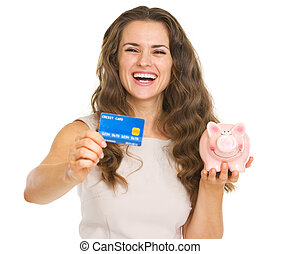 Happy young woman showing credit card and piggy bank