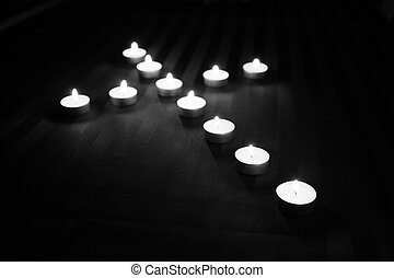 lighted cross - an array of lighted candles in black and...