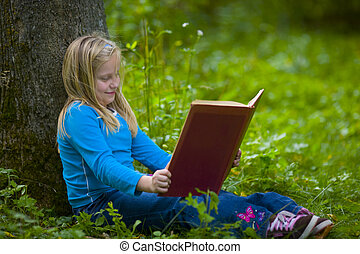 Girl Reading Under a Tree - A girl reading under a tree in a...