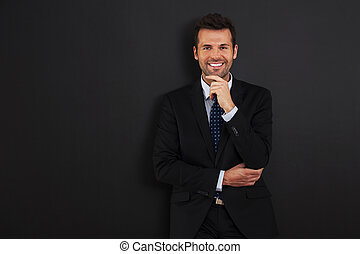 Handsome businessman standing at the blackboard