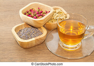 Flowers tea collection in a wooden bowl with cup of tea