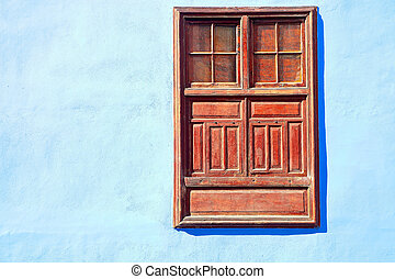 small window  -  Brown wooden window in a painted blue wall