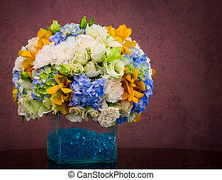 Bouquet of flowers in glass vase on grunge brown background