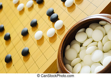 Go stones and board - A game of go Focus on foreground...