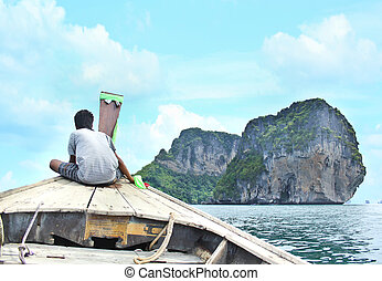 boy sit  on the boat a log the way to the island