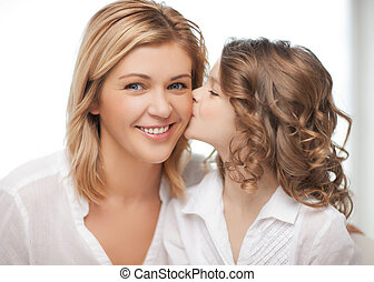 mother and daughter - happy family - daughter kisses her...