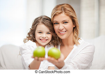 mother and daughter holding green apples - bright picture of...