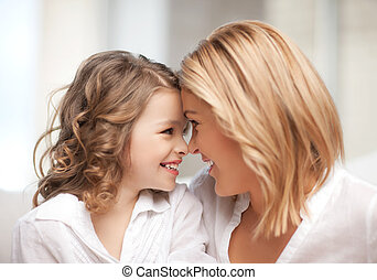 mother and daughter cuddling - bright picture of mother and...