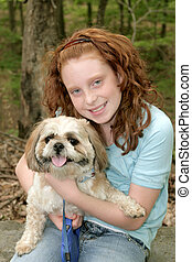 a girl and her dog - young redhaired girl hugging her dog...