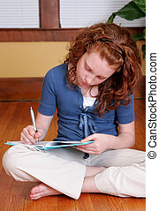 young girl sitting on the floor writing - a young female...