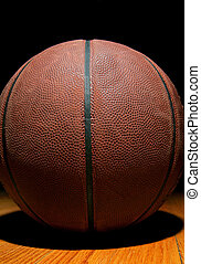 basketball on wood - a brown leather basketball on a...