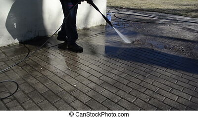 worker wash tiles water - man washes yard tiles.