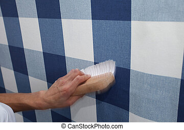 decorator hanging wallpaper with work tool in motion -...