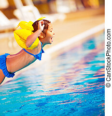 Little girl jumping into the pool, active lifestyle,...