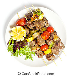 Shish kebab on skewers - Hot roasted meat with onion, tomato...