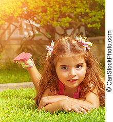 Little girl lying down on green grass - Closeup portrait of...