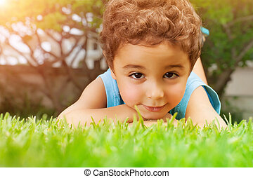 Baby boy lying down on green field - Closeup portrait of...