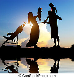happy parents with their little children - Silhouettes of...