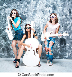 female rock band. girls with musical instruments: cello, sax...