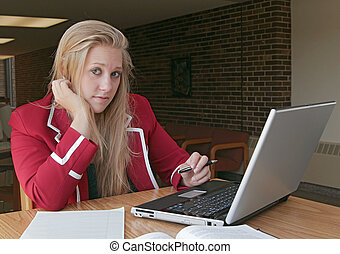 studying young adult - one young female student studying in...