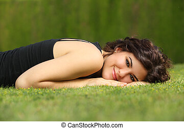 Beautiful woman lying on the grass relaxed and looking at...