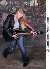 rock star girl - young moody adult female rocker jamming in...