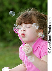 girl blowing bubbles - one young girl child blowing bubbles...