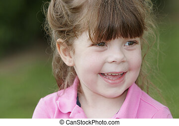 young child smiling - a young child in a pink shirt smiling...