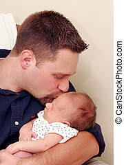 man kissing newborn baby - a father holding his newborn son