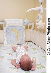 newborn in the crib - a young infant boy in a white crib...