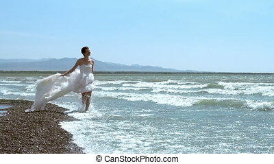Honeymoon at Sea - Woman in a wedding dress walking along...