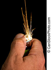 Hand with lighter igniting sparks close-up on dark...