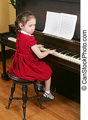 child at the piano - one young child sitting at the piano...