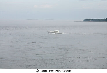 foggy boat sailing - one lonely white boat sailing through...