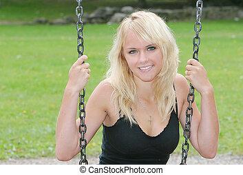 blonde on swing - closeup portrait of a blonde on a swingset...