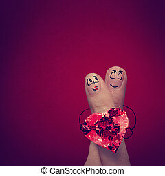 the happy finger couple in love with painted smiley and hold...