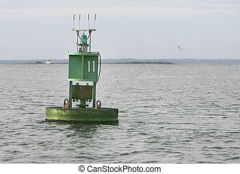 nautical buoy in the water - a green ocean buoy floating in...