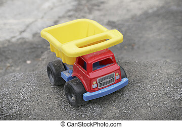 toy truck - one colorful toy dump truck sitting on rocks...