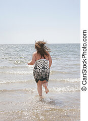 woman in the water - one attractive plus size model running...