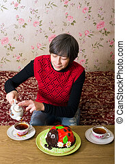 Tea party - The woman sits at the table and pours tea in a...