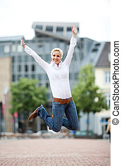 Successful woman leaping outdoors - Successful young blond...