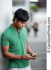 Young man texting - Young man in green polo shirt is texting...