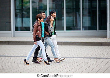 Four Asian friends walking through town - Four trendy young...
