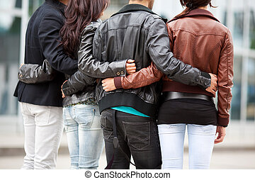 Four friends walking arm in arm - Back view of the mid...