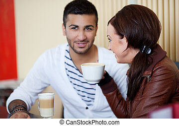 young couple talking in a cafe - beautiful young couple...