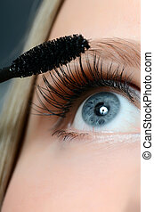 Woman applying mascara on her eyelashes - macro shot - Woman...