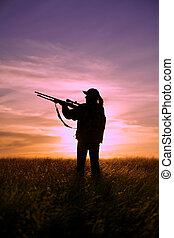 Rifle Hunter at Sunset - a woman rifle hunter silhouetted at...